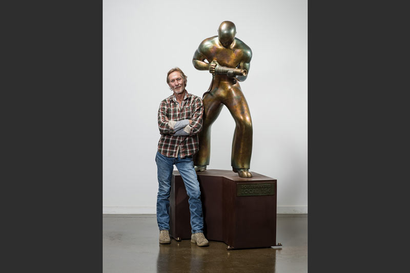 Charles Jones poses with a finished bronze Riveter.