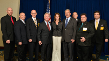 Rep. Cheri Bustos (D-IL-17th), center, with IP Newton Jones, fourth from left; IVP Larry McManamon, sixth from left; IR Bill Staggs, third from right; and l. to r., Brandon Ragland, L-363; Ben Kosiek, L-1; Lew Moceri, L-363; Kirk Cooper, L-60; and Glenn Reinhardt, L-483.