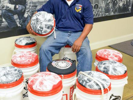 GIKUS BIGELOW, un miembro del L-456, se sienta entre cubos de herramientas que él donó a los concursantes en la Competencia Nacional de Aprendizaje Boilermaker 2015.