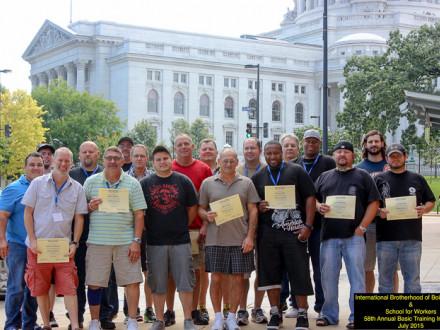 Los egresados del curso básico del 58o Instituto Anual de Verano en Madison, Wisconsin, de pie con sus certificados frente al Capitolio el 17 de julio.