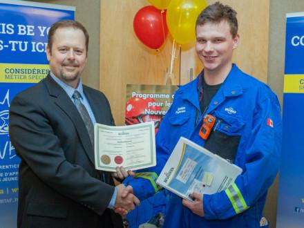 Michael Barnett, director de Certificación de Aprendizaje y Ocupación de New Brunswick, a la izquierda, premia a Sheldon Patterson del L-73 con su certificado de Sello Rojo.