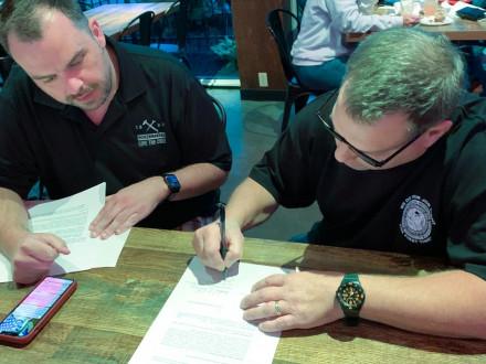 El director ejecutivo de las Operaciones del Sector Industrial, Tyler Brown, y Mike DeDomenic, presidente del nuevo sindicato de los Boilermakers en Honeywell, revisan los documentos de afiliación.