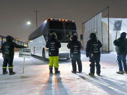 A pesar de las temperaturas de -20F/-29C, los Boilermakers excluidos del L-146 se mantienen firmes en la línea de piquete mientras se acerca un autobús lleno de trabajadores sustitutos.  La sede sindical Internacional ha proporcionado abrigos y pantalones de nieve para mantener a los Boilermakers calientes en la línea de piquete.