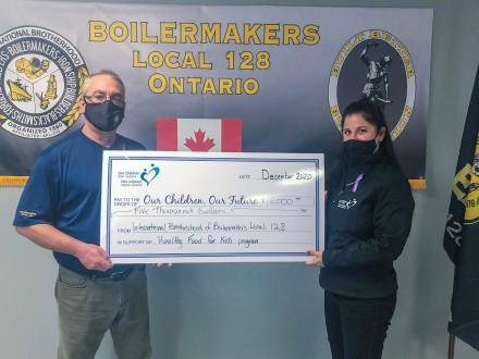 El agente de negocios del L-128 Joe Duprey entrega cinco mil dólares de parte del L-128 a Our Children Our Future en Sudbury.