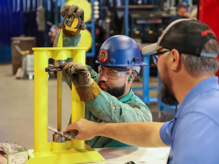 El participante de la Competencia de Aprendizaje del Área Noreste L-5 Z-5, Ruddy Fernández, mide para determinar la longitud de un tubo.