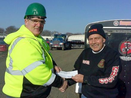 Don Hartney, del L-29, le entrega a Tony Gatro, representante de Juguetes para Niños, un cheque por más de $ 1,200 dólares.