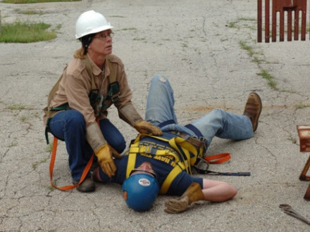 "Apprentice Brenda Healey, Local 83 (Kansas City), responds to fellow apprentice Matthew ""Scooter"" Payne, Local 592 (Tulsa, Okla.), who plays the role of an injured worker."