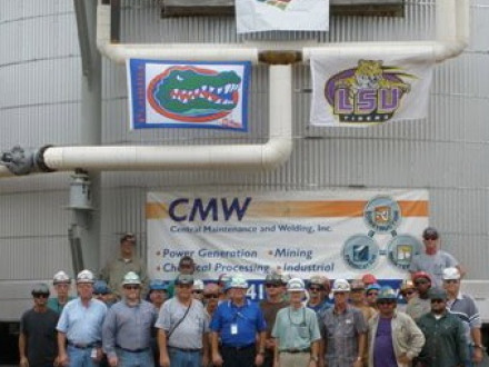 Members of Louisiana L-37 and Florida L-433 stand in front of a converter they built, displaying flags of their favorite college teams.