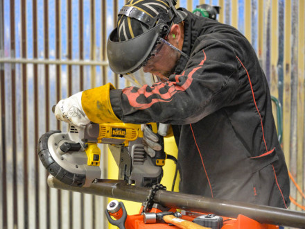 """Arthur Kling, L-13, cuts out a short piece of replacement tube, called a """"pup,"""" during the waterwall exercise in 2014 at the Boilermaker National Apprenticeship competition, where he captured top honors. With the Biden Administration ending IRAPs, union apprenticeship programs such as BNAP remain the gold standard in training."""