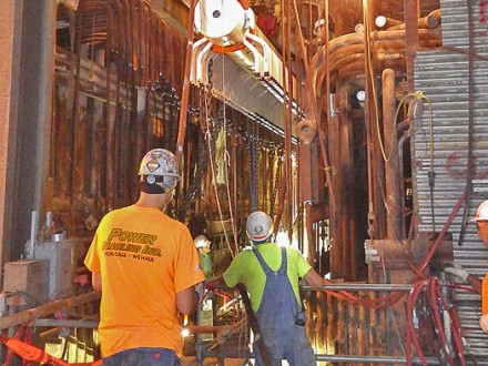 CAREFULLY – The new, five-story superheater header is hoisted by Boilermakers Local 27 members through an opening cut into the side of the building where the 17-story boiler is located.
