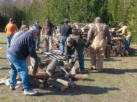 Local D351 members and other volunteers stack wood for Wayne Woloszyk in Posen, Mich.
