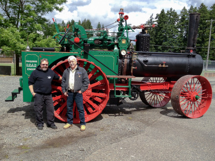 Barry Dobrensky, left, and Mike Roxburgh stand alongside the 1917 Farquhar tractor they helped restore.