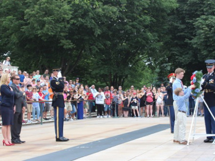 Bridget Martin and her husband, Bryan, watch as their sons, Bryce and Brody, receive the wreath prior to setting it at the tomb.