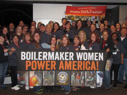 The Boilermakers' contingent at the Women Build Nations conference holds up a banner to show their pride and solidarity.
