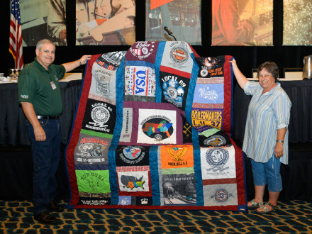 JoBeth Allison displays the quilt she made to support the Disaster Relief Fund. At left is Director of Health and Safety Services Mark Garrett.