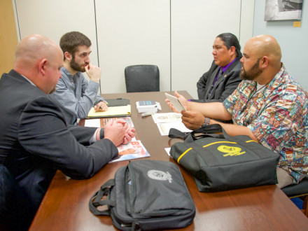 "Local 627's Shane ""Kalai"" Ferreira, who works for BAE Systems in Hawaii, offers reasons why a strong Jones Act is essential to the nation. L to r: BM-ST Jacob Evenson; Jesse Isleman, legislative aide of Sen. Brian Schatz (D-HI); Wesley Dale and Ferreira."