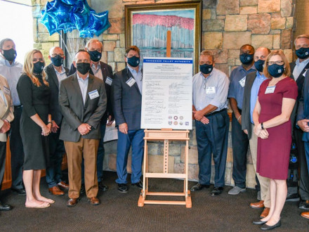 Representatives from both the TVA and labor unions further their partnership with a 10-year contract extension. Left of the sign, front row from l. to r., Megan Flynn and Mike Skaggs. Back row l. to r. David Tolley, UA; Brandon Bishop, administrator Hourly Council; Curtis Sharpe, IBEW; David Beckler, administrator Annual Council and Jeff Lyash, TVA. Right of the sign, front row, Sue Collins, TVA. Back row l. to r., IR Dusty Garmon; Mark Holt, Laborers; Will Trumm, TVA; Keith McFarland, Machinists and Chip S