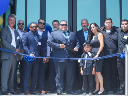Dignitaries prepare to cut the ribbon, officially opening the Oscar Davila Training Center, l. to r., Western States Contractor Coordinator Larry Jansen;Western States Joint Apprenticeship Area CoordinatorCollin Keisling; L-92 Welding Instructor Hugo Castañeda; L-92 Apprenticeship Coordinator Alfredo Leyva; IVP-WS J. Tom Baca; L-92 BM-ST Luis Miramontes; IVP-GL Lawrence McManamon; and Irma Davila, flanked by the Davila's sons Octavio, Omar and Oscar.