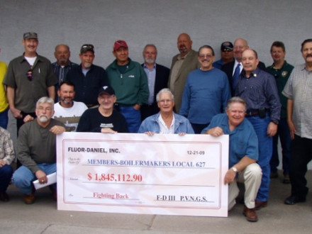 Local 627 members display a mock check representing their portion of a $12 million settlement with Fluor Daniel. Joining in the presentation are, standing, BM-ST Allen Meyers, third from right; Blake & Uhlig attorney Mike Stapp, fourth from right; D-CRS/AIP Gary Evenson, seventh from right; and IST Bill Creeden, eighth from right.