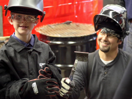 A young Scout shows his excitement after welding his initials in plate steel. Holding up the handiwork is L-101 member Vince Sheely.