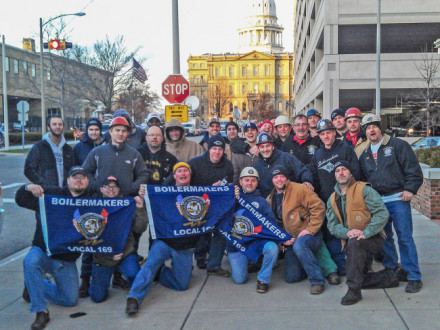 A contingent from L-169 gathers in Lansing. The stop sign separating the group from the capitol seems appropriate, given the assault on unions orchestrated by Republican lawmakers and Gov. Snyder.