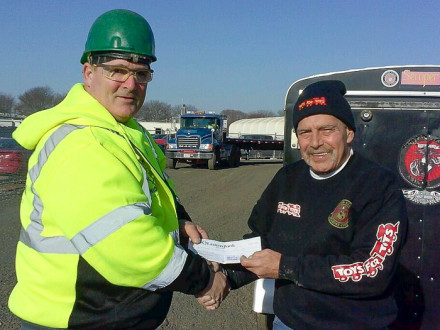 Don Hartney, L-29, left, gives Toys for Tots representative Tony Gatro a check for over $1,200.