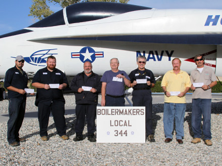 With an F/A-18 Hornet as a backdrop, seven members of Local 344 display