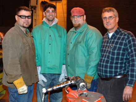 """Career-seeker Daniel Seddiqui, second from left, gets some first-hand experience with a tube beveling machine at Local 83 in Kansas City, Mo. From left are welding instructor Mike Anderson, Seddiqui, welding instructor Clayton """"Lumpy"""" Knepp, and BM-ST Randy Cruse."""