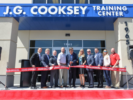 Jim Cooksey cuts the ceremonial red ribbon to signify the center's official opening. l. to r. WSJAC Assistant Coordinator Andrew Jones, BOL President Bob McCall, SBCTC President Robbie Hunter, WSJAC Area Coordinator Collin Keisling, Cooksey, Charmayne Cooksey, IP Newton Jones, IVP Tom Baca, and Jenny Farney and Dan Klingman of Lincoln Electric.