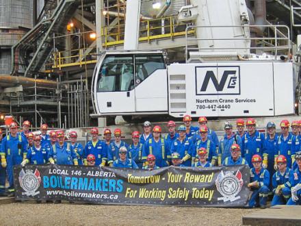 The night shift crew shows its pride. L. to r., Denis Lafleur, L-146; Syncrude Coordinator Alwyn Reese; Mike Queen, L-128; Michael Shelton, L-263; Gary Joy, L-667; John Eagle, L-73; Anthony Carlton, L-128; Mike Bragg, L-667; Steve Myers, L-83; Ulysse Godin, L-73; Fred Davis, L-11; Bill Wallace, L-359; Jason Forman, L-105, Brent Bell, L-105; Brent Bernosky, L-359; Larry Brown, L-191; Diandra Tompkins, L-128; Ryan Woods, L-110; Allard Lanteine, L-73; John Allen, L-263; Darren Robicheau, L-73; Greg McCarthy, L
