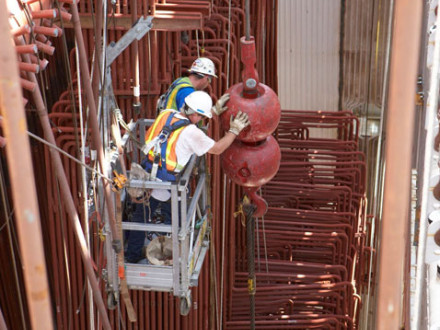 Two Boilermakers help direct a tube section lift. Photo courtesy of MOST/Martin Communications