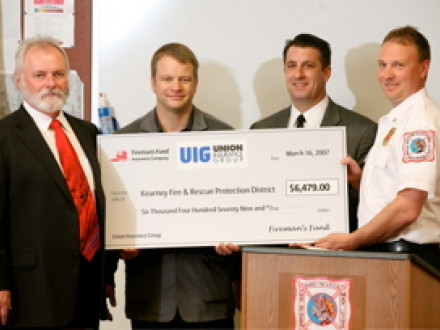 IST Bill Creeden, left, joins in a check presentation to the Kearny, Mo., Fire Protection District. L. to r. are Chris DeCaigny, president of the Union Insurance Group; Rick Victores, field vice president for Fireman's Fund Insurance; and Captain Kevin Pratt of the Kearny FPD.