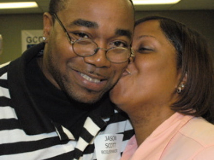 Jason Scott gets a congratulatory kiss from his wife after graduating from an AFL-CIO-sponsored career education and orientation program.