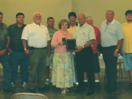 Local 112 presents an award to United Way liaison Pat Rabbeitt. L. to r., J.M Crane, H.M. Turner, Dennis King, W.E. McDaniel, Mrs. Rabbeitt, John Nolen, C.T. Brooks, Don J. Staples, H.E. Turner, and H.E. Turner Jr.