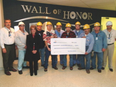 Pictured (l. to r.) with a check for $8,270 are Dresden plant mgr. Dave Wozniak, L-17 steward Jim Bollin (Insulators), Deborah Trippiedi of Mom's Cookies, L-1 steward Brett Hamilton (Boilermakers), L-916 steward Rick Wren (Carpenters), L-75 steward Paul Colabuono (Laborers), job site rep Jim Carpenter (L-1, Boilermakers), L-176 steward Mike Barkley (IBEW), L-444 steward Paul Falasca (Ironworkers), L-597 steward Bob Polancic (Pipe Fitters), and Stone & Webster site mgr. Graham Cross.