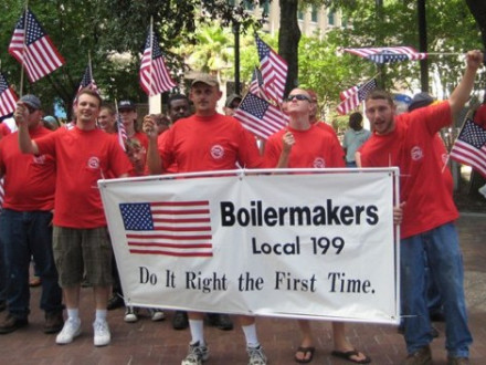 Holding a banner at the Jacksonville, Fla., Flag Day parade with SAJAC instructor Eric Olson (second from left) are first-year apprentices (l. to r.) Glen Wiley, Matt Hersey, and Warren Bush.