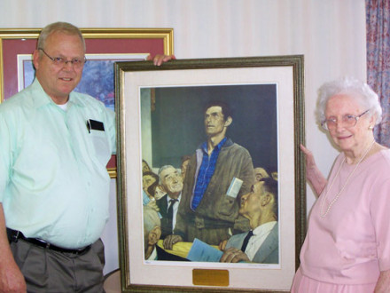 """Mrs. Marie B. McDonough presents a framed copy of Norman Rockwell's """"Freedom of Speech"""" print to L-1 BM-ST John Skermont."""
