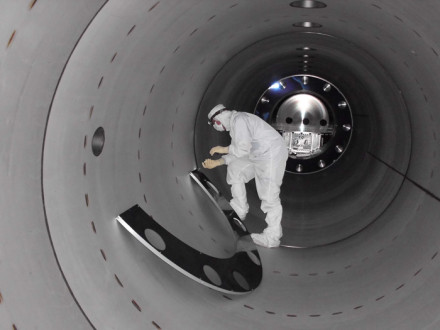 """A technician at the Laser Interferometer Gravitational-Wave Observatory installs a mode cleaner tube baffle. Boilermakers built five miles of special tubes for each of the observatory's twin """"detector sites"""" in Hanford, Wash., and Livingston, La. Scientists there recently announced a major breakthrough proving a key part of Einstein's general theory of relativity. Caltech/MIT/LIGO Lab"""