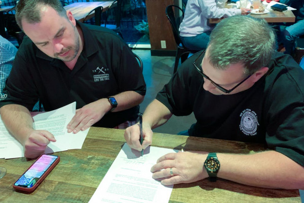 ISO Executive Director Tyler Brown and Mike DeDomenic, president of the new Boilermaker-affiliated union at Honeywell, review the affiliation paperwork.