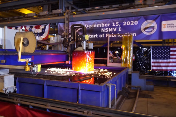A plasma cutting machine makes the first cut in a steel plate.  The pieces will be transported to an assembly line where they will eventually become part of the ship's keel.