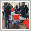 En la foto de arriba, el director de Servicios de Organización, Jody Mauller, le da una camiseta a Kacee Holland, miembro del S251.