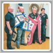 Dos miembros jubilados del L-60 reciben una colcha hecha a mano por parte de la organización sin fines de lucro Quilts of Valor para agradecerles por su servicio durante la guerra de Vietnam. De izq. a der.: Rod Johnson; del L-60, John Williams y Jack Cooper; y Terry Johnson.