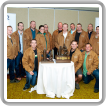 Contestants try on commemorative jackets during a reception. Kneeling, l. to r., Alexandre LaPalme-Lajeunesse, L-271; Joe Beauchamp, L-128; and Sean Walsh, L-203. Standing, l. to r., Ross Thompson, L-359; Brian Loos, L-359; Justin Brkic, L-73; Nathalie Delisle, L-271; Cory Malakoff, L-555; Roger McGuire, L-555; Paul Salisbury, L-128; James Mason, L-203; Dixon Lewis, L-73; Clayton Chiurka, L-146; and Neil Bennett, L-146.