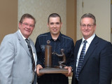 Local 73's Jason Matteau accepts the first-place trophy from Industry Award of Excellence winner Fabian Tompkins, l., with Canadian National Apprentice Coordinator Grant Jacobs at right.