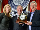 IP Newton B. Jones, center, presents a clock to commemorate IVP Jim Pressley's 50 years of service during the LEAP conference last year. At left is Bridget Martin, Director of Political Affairs.