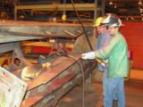 Apprentice Justin McGilton, r., builds a locomotive snow plow under the watchful eye of journeyman Jeff Matzek.