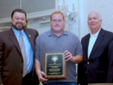 Local 182 acting BM-ST Casey Tibbs, center, accepts the national NACBE safety award as IVP Tom Baca (Western States), l., and NACBE Exec. Dir. John Erickson join in the presentation.