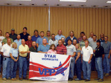 Senco representatives display the STAR banner they earned at the Marathon Petroleum Co. in Robinson, Ill. Pictured behind the banner, beginning fourth from left, are Senco officers Don Bickers, vice president; Steve Neeley, CEO/owner; and Resa Shaner, president. In the third row, second, third, and sixth from left respectively, are NTL Boilermaker foremen Tom Farrar and Tim Midgett, and NTL Boilermaker steward Guy Tewell. (Photo by Tom Compton)