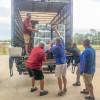 L-37 members unload a pallet of paper towels.